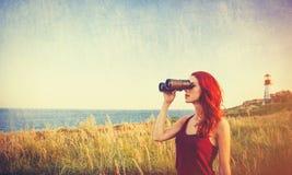 Girl with binocular near Lighthouse Royalty Free Stock Photo