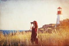 Girl with binocular near Lighthouse Royalty Free Stock Image