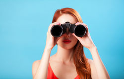 Girl with binocular. Redhead girl with binocular on blue background stock photography