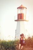 Girl with binocular sitting on the grass near Lighthouse Royalty Free Stock Photography