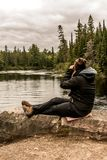 Girl with binocular sitting near Lake of two rivers in Algonquin National Park Canada Ontario natural pinetree landscape. Girl with binocular sitting near the Stock Photo