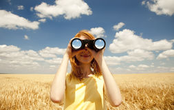 Girl with binocular at wheat field. Royalty Free Stock Photography