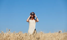 Girl with binocular at wheat field. Royalty Free Stock Photos