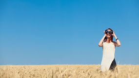 Girl with binocular at wheat field. Stock Photography