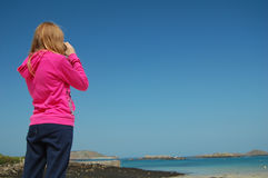 Girl with binoculars. Young girl with binoculars looking out to sea Stock Photos