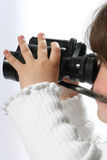 Girl with binoculars. Side portrait of young girl with pair of modern binoculars, white background Stock Photo