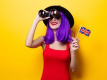 Girl with binoculars and Great Britain flag. Portrait of young style hipster girl with purple hairstyle with binoculars and Great Britain flag in hand on yellow Royalty Free Stock Photo