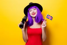 Girl with binoculars and Great Britain flag. Portrait of young style hipster girl with purple hairstyle with binoculars and Great Britain flag in hand on yellow Stock Photo