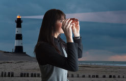 Girl with binoculars and lighthouse in twilight stock images