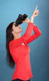 Girl with the binoculars pointing upward Stock Image