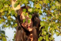 Girl among birch foliage Royalty Free Stock Image