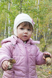 Girl in a birch forest holding a mushroom. Stock Images