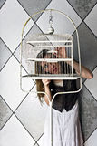 Girl with Birdcage. A girl looking into an empty, antique birdcage Royalty Free Stock Images