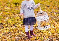 Girl with birdcage Stock Photos