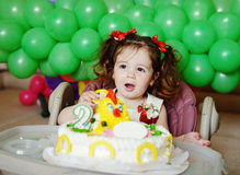 Girl and birthday cake. Happy toddler girl and her birthday cake stock photo