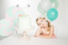 Girl with birthday cake. Smiling little girl sitting at table with birthday cake Royalty Free Stock Photos