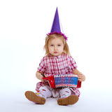 Girl with birthday cap playing accordion Royalty Free Stock Photo