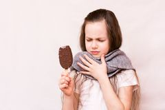 The girl bit off the ice cream and her throat ached royalty free stock photo