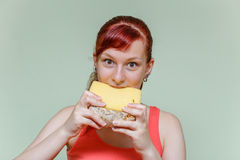 Girl bites cheddar cheese Royalty Free Stock Photo