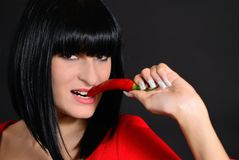 The girl bites hot pepper Stock Image