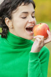 Girl bites off an apple Royalty Free Stock Photos