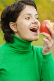 Girl bites off an apple Royalty Free Stock Photography