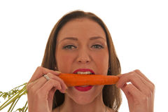Girl bites an orange carrot Stock Photography