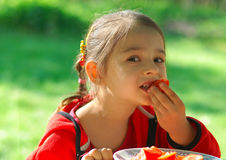 Girl bites tomato. The little girl sits at table in garden and eats tomato Stock Photos