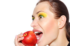 Girl biting apple. Beautiful funny model biting apple. Healthy eating. Funny royalty free stock images