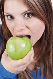 Girl biting an apple Royalty Free Stock Images