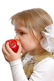 The girl biting an apple on a white. Background Royalty Free Stock Image