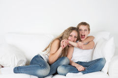 Girl biting a boy's hand. Children sit on the couch and fight Royalty Free Stock Image