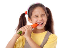 Girl biting the carrot Royalty Free Stock Image