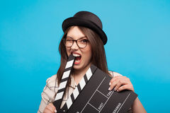 Girl biting clapboard. Young woman in hat and glasses biting clapboard and looking at camera on blue background royalty free stock photography