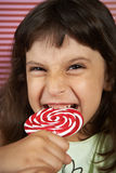 Girl biting furiously a large lollipop Stock Photography