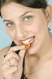 Girl biting gold coin stock photography