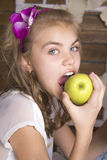 The girl biting a green apple. A head band with flower . teen girl Royalty Free Stock Image