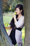 Girl  biting a green apple leaning on a tree Stock Photos