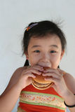 Girl biting hamburger. Little chinese girl holding and biting a hamburger Royalty Free Stock Photos