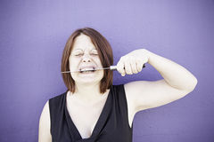 Girl biting knife Stock Photos