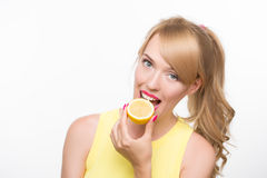 Girl biting a lemon. On a white background royalty free stock photography