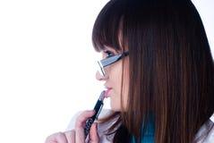 Girl biting pen Royalty Free Stock Photos