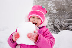 Girl biting piece of snow Royalty Free Stock Photo