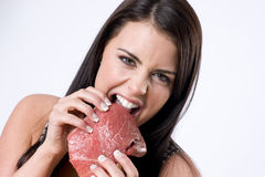Girl biting raw red cow meat sirloin steak Royalty Free Stock Photography