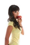 Girl biting into a red apple stock image