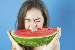 Girl biting a slice of watermelon. Stock Photography