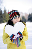 Girl bitten snowy heart. Standing in a park in the yellow jacket Stock Photos