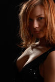 Girl in black. Girl with large bosom in black on black Royalty Free Stock Image