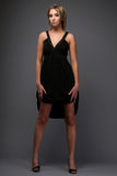 Girl in black. Dress posing on grey background Stock Photography