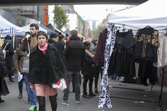 The girl in a black artificial fur coat chooses to itself clothes in a street market Royalty Free Stock Images